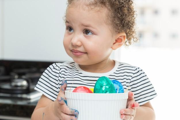 Diverse uova di pasqua in mano a un bambino.