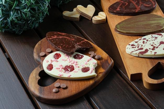 Diversi cioccolatini a forma di uovo su un legno. accanto alle gocce di cioccolato,