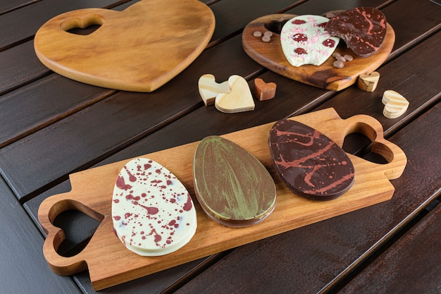 Diversi cioccolatini a forma di uovo su un legno. circondato da cuori di legno.