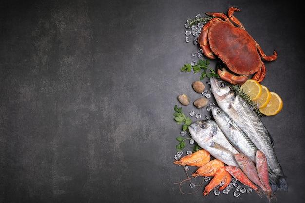 Diversi pesci, granchi e conchiglie su uno sfondo nero con spazio per scrivere