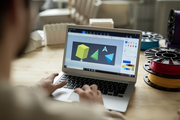 Diverse forme geometriche sul display del laptop e le mani del designer creativo sulla tastiera durante il lavoro in ufficio