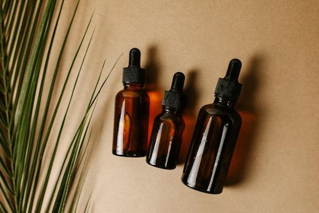 Diversi vasi di vetro con pipette con siero idratante su uno sfondo marrone con una foglia di palma. il concetto di estratti tropicali nei cosmetici