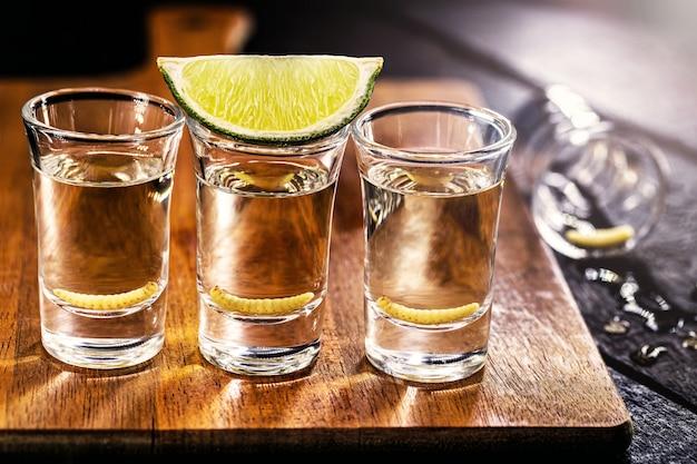 Diversi bicchieri di mezcal (o mezcal), brandy tipico ed esotico del messico, con larva in superficie e limone