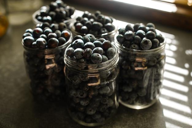Diversi barattoli pieni di mirtilli raccolti o bacche di caprifoglio sul tavolo della cucina alla luce del sole.