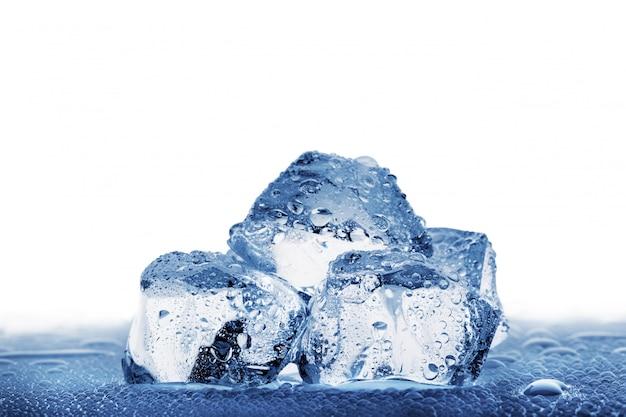Diversi grandi cubetti di ghiaccio con goccioline sul tavolo bagnato