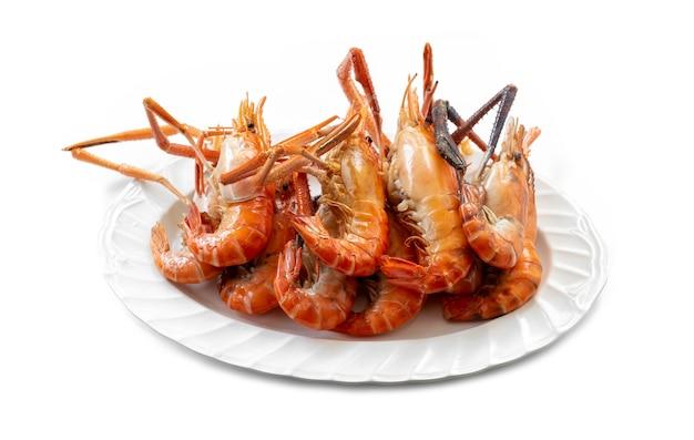 Diversi gamberoni di fiume di grandi dimensioni grigliati e posti su un piatto sono pronti da mangiare su sfondo bianco.