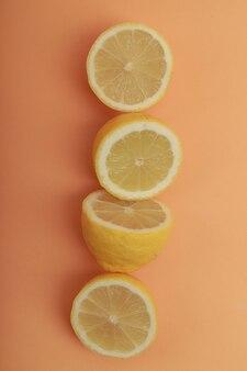 Diversi limoni allineati su uno sfondo arancione pastello