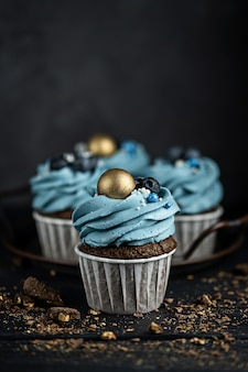 Diversi muffin o cupcakes con crema a forma di blu e con mirtilli al tavolo nero su uno sfondo scuro. copyspace stile rustico.
