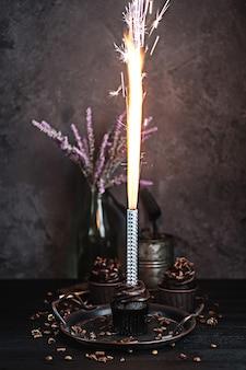 Diversi muffin o cupcakes con crema al cioccolato a forma di tavola nera. candele festive brucia su una torta al cioccolato.