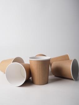 Diverse tazze di carta marrone usa e getta sono posizionate in modo casuale su uno sfondo bianco.