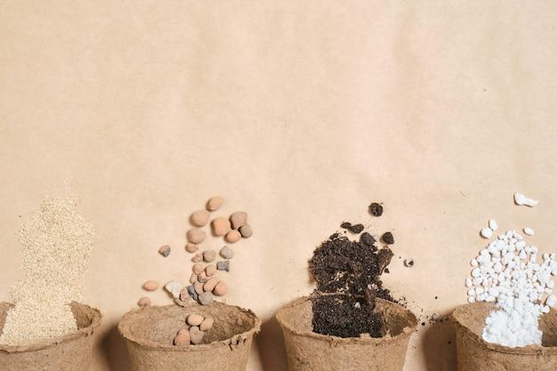 Diversi vasi di torba con diversi ingredienti per preparare terreno fertile per piante, pietre per drenaggio, perlite, terreno per piantine, fertilizzante per il giardino