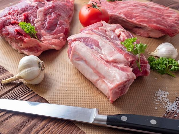 Diversi pezzi di carne cruda fresca sono sparsi su pergamena. accanto all'aglio, le erbe aromatiche, i pomodori e il coltello. vista laterale.