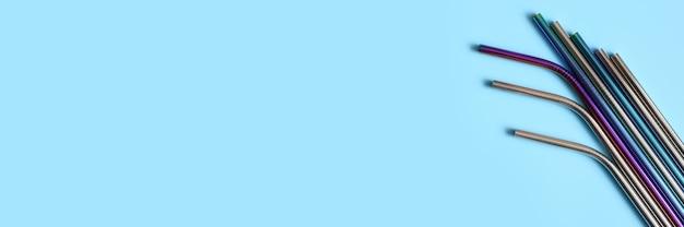 Diverse cannucce riutilizzabili in metallo in acciaio inox su sfondo blu. spazio per il testo. banner