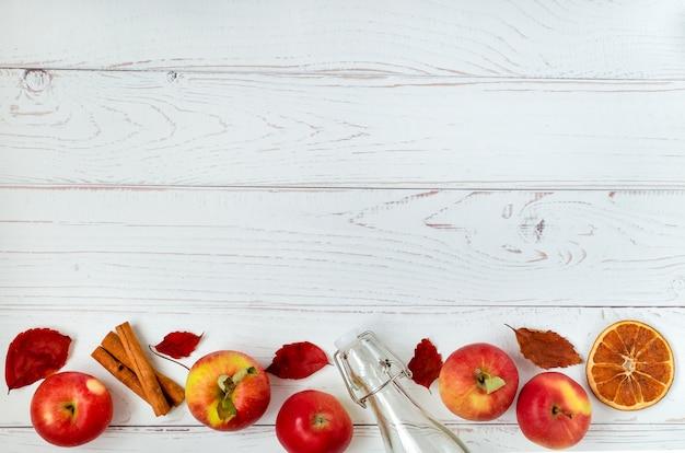 Diverse mele rosse mature, spezie, bottiglia di vetro e foglie di autunno su una superficie leggera.
