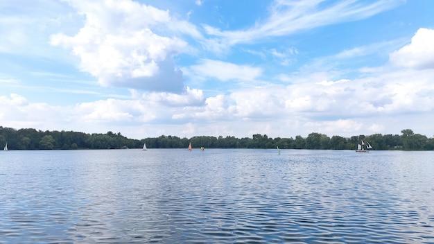 Diverse barche a vela su un bellissimo lago blu. cielo blu con soffici nuvole bianche, estate e piacevole sfondo verde del paesaggio.