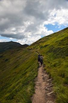 Diversi viaggiatori che camminano lungo il crinale fino alla cima della montagna contro il cielo blu