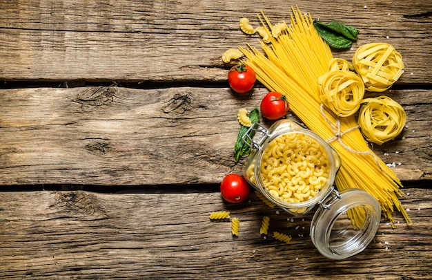 Diversi tipi di pasta secca con pomodoro ed erbe aromatiche. sulla tavola di legno. spazio libero per il testo. vista dall'alto