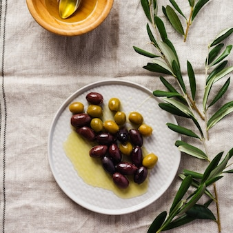 Diverse varietà di olive fresche in diversi piatti di ceramica su una vecchia tovaglia tovagliolo grigio vintage. concetto di prodotto naturale. set di posate vintage rustico. vista dall'alto, copia dello spazio.