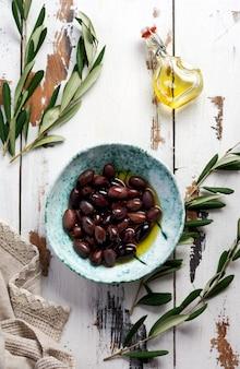 Diverse varietà di olive fresche in diversi piatti di ceramica su un vecchio sfondo grigio vintage tovaglia tovaglia. concetto di prodotto naturale. servizio di posate vintage rustico. vista dall'alto, copia spazio