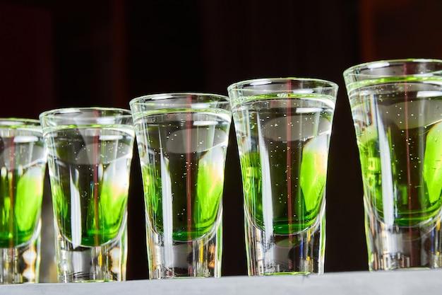 Diversi bicchierini di bevande alcoliche bianco-verdi sul bancone del bar