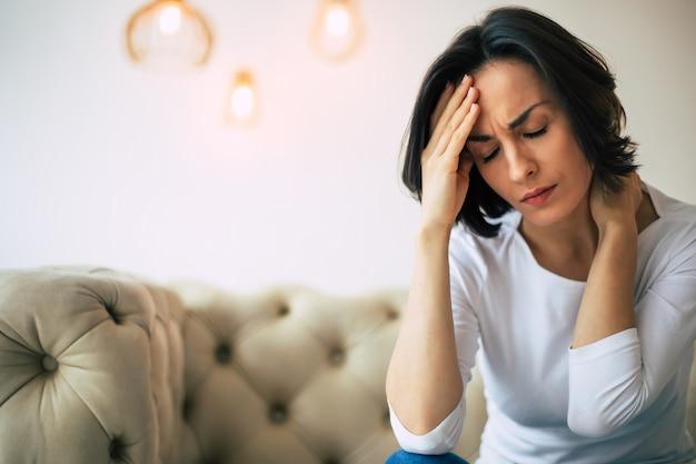 Dolore intenso. foto ravvicinata di una bella donna, che si tocca la fronte e la nuca, mentre soffre di mal di testa.