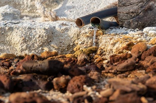 Scarichi delle acque reflue e delle acque reflue sulla spiaggia di sabbia