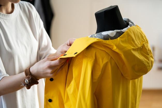 Lavori di fognatura con manichino che regola l'impermeabile alla moda su un sarto fittizio in fashion design studio
