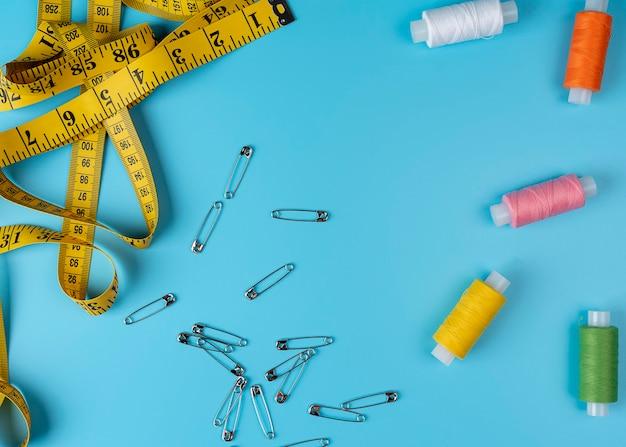 Accessori per cucire e tessuto su sfondo blu. filati per cucire, spille, tessuto, bottoni e centimetro per cucire. vista dall'alto, disposizione piatta