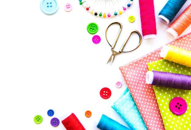 Accessori per cucire e tessuto su uno sfondo bianco