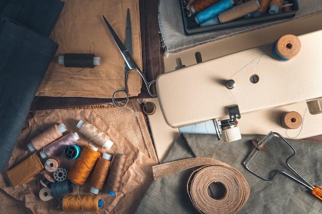 Accessori per cucire e macchina da cucire su sfondo vintage.