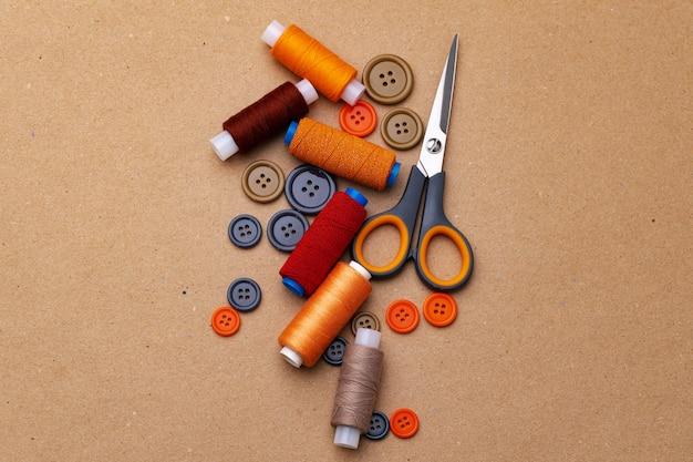Bottoni da cucire e forbici su fondo beige