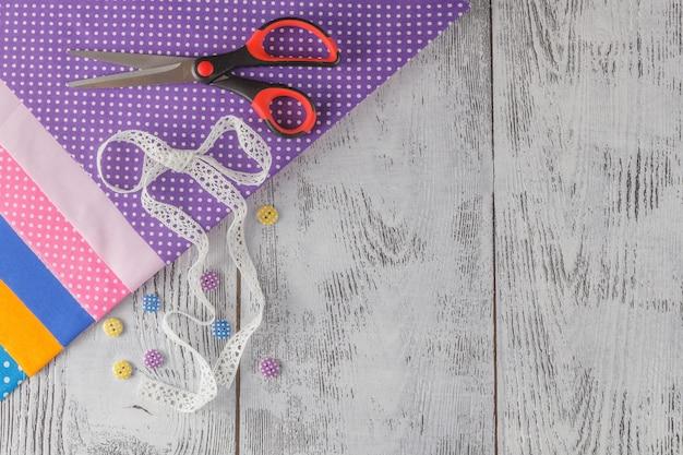 Accessori per cucire, lavorare a maglia e uncinetto. tessuto, tavolo in legno. copia spazio