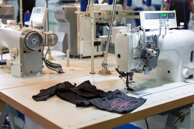 Macchina da cucire e stoffa nel negozio di taglio, nessuno, fabbrica di abbigliamento. produzione di tessuti, cucitura, tecnologia del ricamo