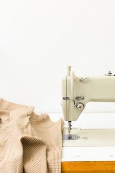 Macchina da cucire e tessuto su sfondo chiaro