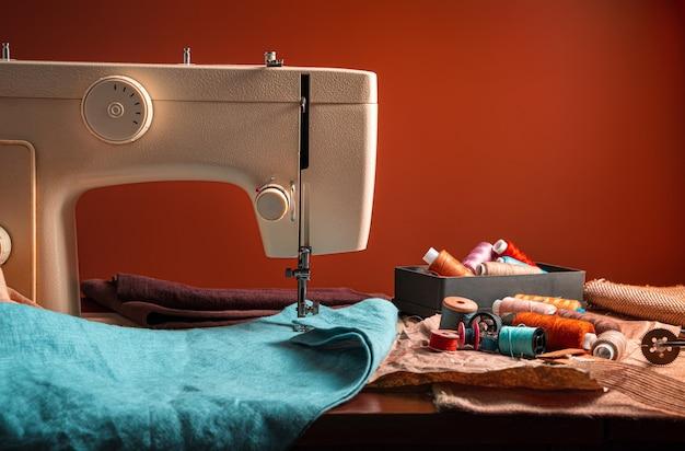 Macchina da cucire e accessori per cucire su uno sfondo marrone. il concetto di cucito.