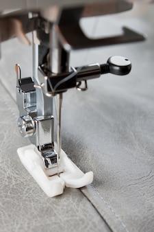 La macchina da cucire con piedino speciale esegue una cucitura sulla pelle grigia. processo di cucito da vicino
