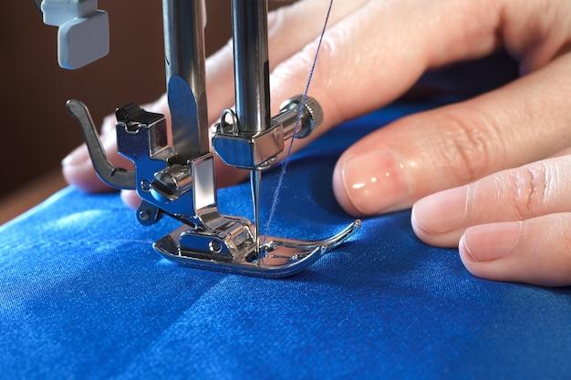 Processo di cucito, le mani delle donne dietro il suo lavoro sulla macchina da cucire, vista laterale del primo piano