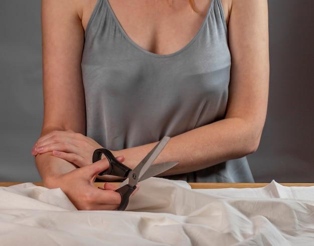 Forbici da cucito in mani di sarto che iniziano a lavorare con materiale di cotone