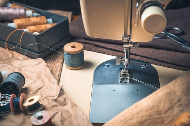 Posto di lavoro di cucito con macchina da cucire e filo.