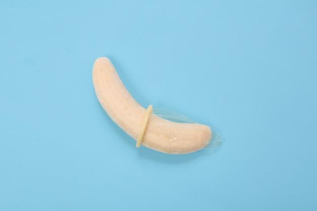 Educazione sessuale con banana e preservativo isolato su sfondo blu