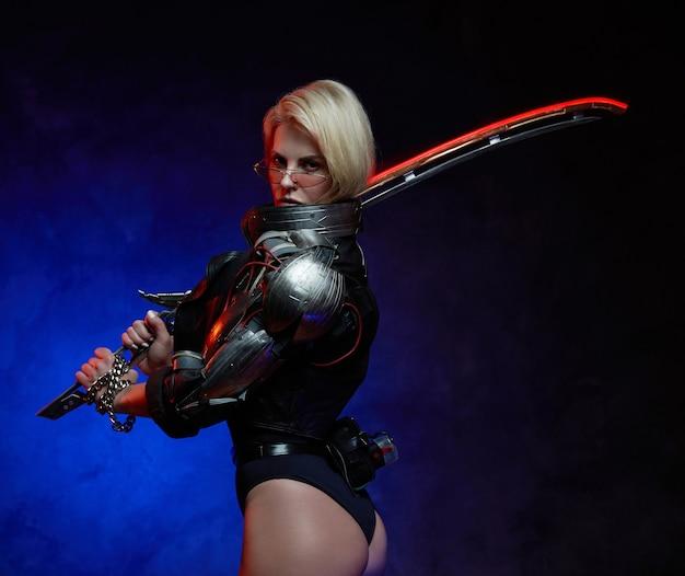 Sessuale e cibernetica donna soldato con i capelli biondi vestita con giacca di pelle nera e tenendo la lama.