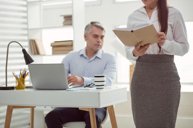 Oggetto sessuale. messa a fuoco selettiva di una donna attraente in piedi in ufficio e leggendo il libro pur essendo oggetto di interesse sessuale