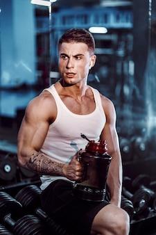 Un uomo allenato sessualmente beve l'alimentazione sportiva dopo un forte allenamento, mani, piedi, schiena, bicipiti e tricipiti