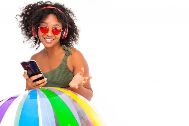 La donna africana sexy in occhiali da sole e un costume da bagno tiene il telefono in mano e ascolta la musica