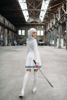 Donna bionda in stile anime sexy con spada, vista posteriore. moda cosplay, cultura giapponese, bambola con lama su fabbrica abbandonata