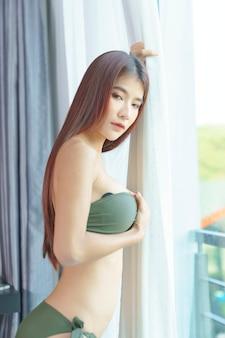 Donna asiatica sexy in bikini verde in camera da letto in vacanza