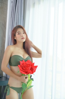 Donna asiatica sexy in bikini verde che tiene rosa rossa in camera da letto
