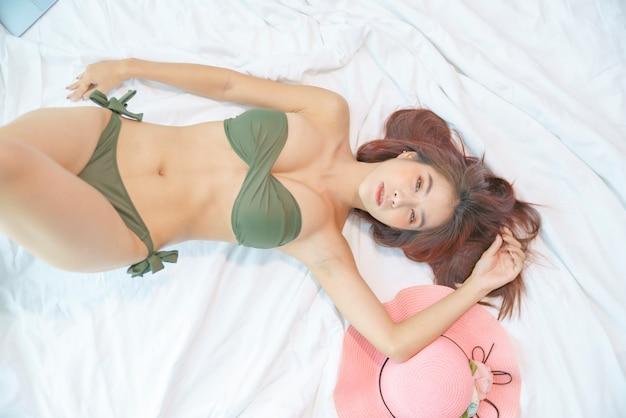 Donna asiatica sexy in bikini verde sdraiato sul letto