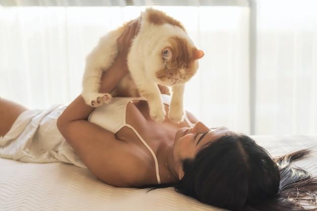 La donna asiatica sexy in biancheria gioca con il gatto esotico giallo dello shorthair sul letto al tramonto. rilassati e allegra attività con un adorabile animale domestico.