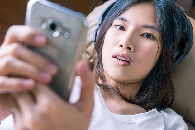 Le donne asiatiche sexy sta ascoltando musica sul telefono cellulare